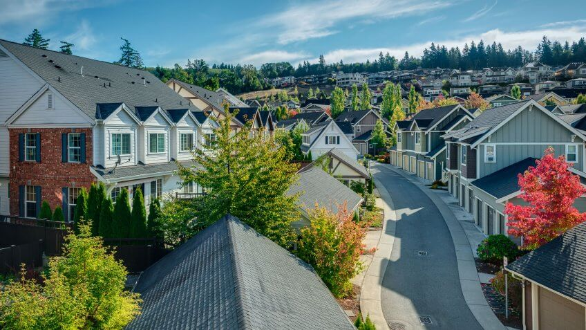 Houses line a Curvy Road that cuts through Residential Neighborhoods in the Issaquah Highlands on an Autumn Morning.