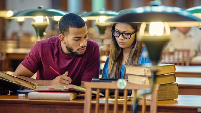 African american College student and asian girl using a digital tablet for doing research in the lecture room.