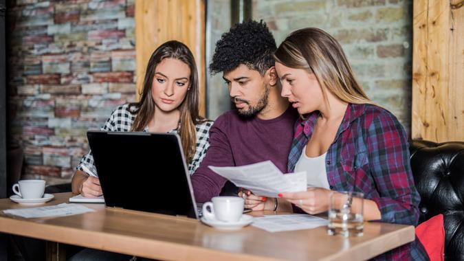 Young multi-ethnic group of people doing a research on student loans.