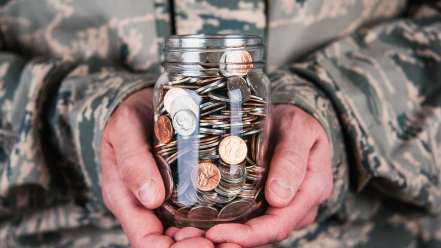 US military serviceman holding jar full of coins.