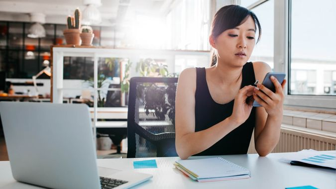 woman sitting at her desk with laptop and adhesive notes using mobile phone.
