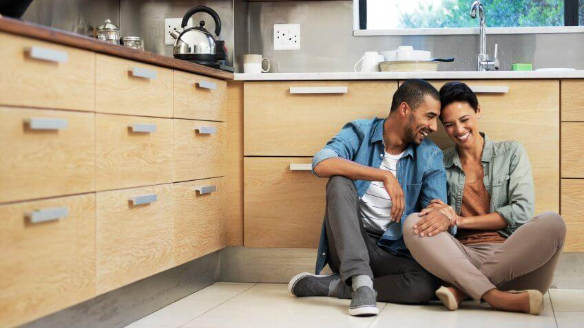 Shot of a smiling young couple sitting together on their kitchen floor.