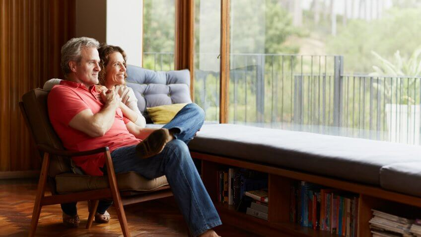 Thoughtful mature couple relaxing by window at home.