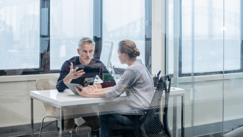Businessman and businesswoman sitting at desk in modern office, in discussion.