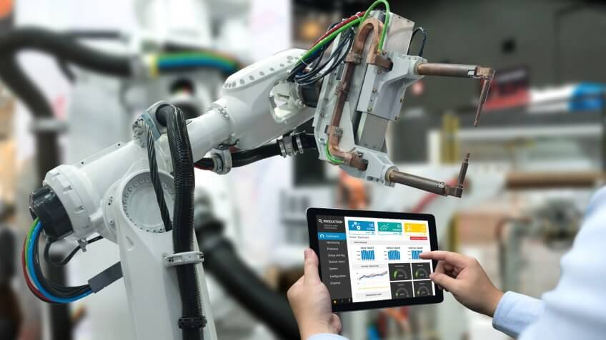 Engineer hand using tablet, heavy automation robot arm machine in smart factory industrial with tablet real time monitoring system application.