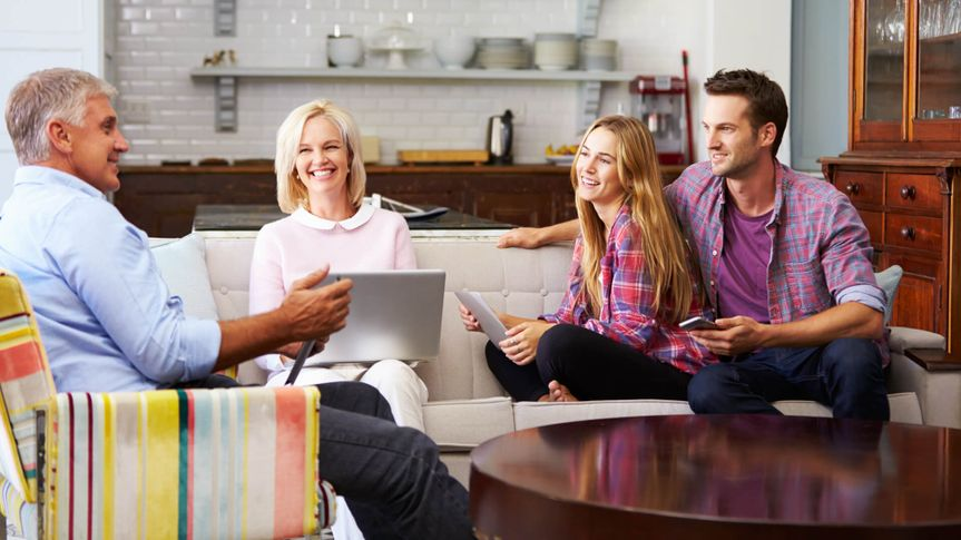 Parents With Adult Offspring Using Digital Devices At Home.