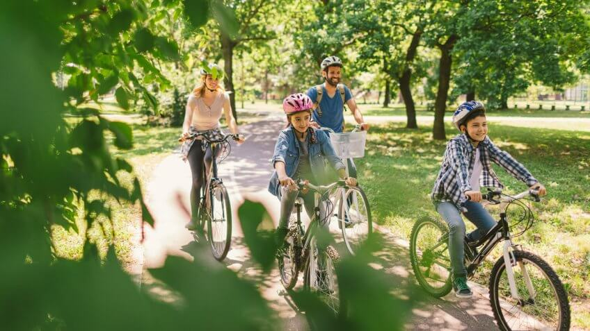 Family riding bicycle in the public park together.