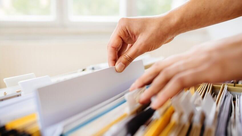 hand filing financial paperwork