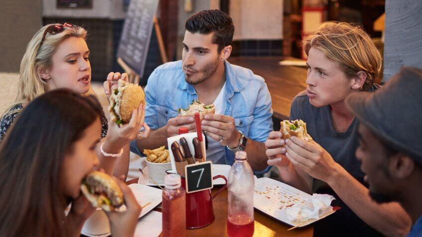 Young male and female friends having burgers in restaurant.