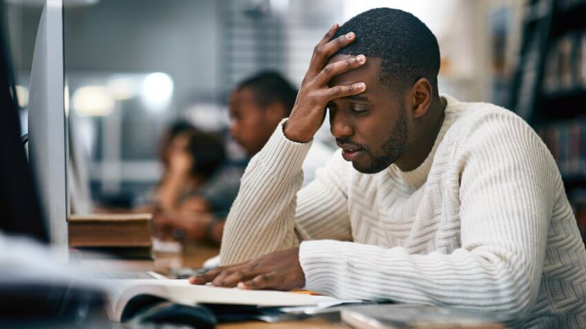 Shot of a young man studying in a college library and looking stressed.