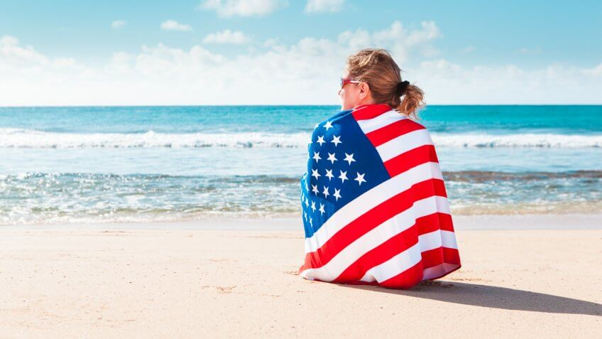 Caucasian woman wrapped in USA flag towel, sitting on an idyllic tropical paradise beach.