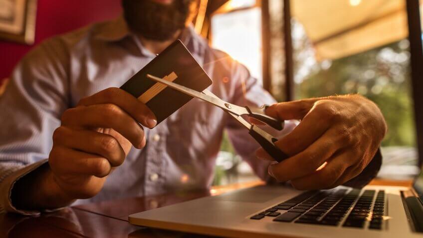 man cutting up credit card