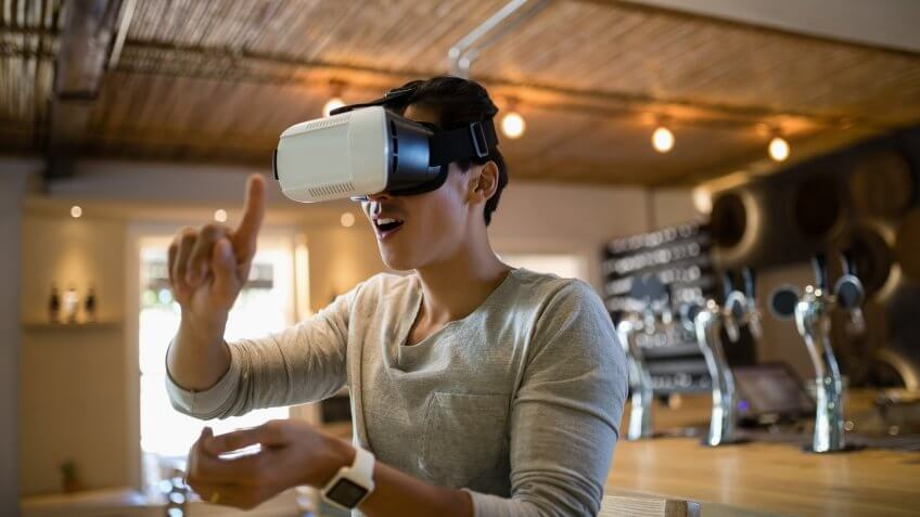 Smiling man using virtual reality headset in restaurant.