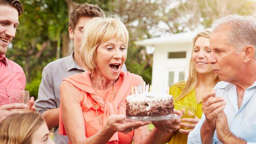 Multi Generation Family Celebrating Birthday In Garden.