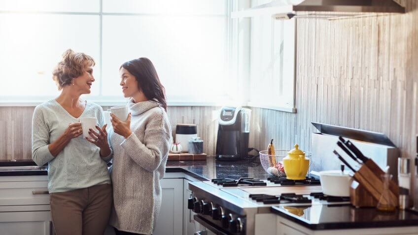Shot of a young woman enjoying a coffee break and chat in the kitchen with her mother at home.