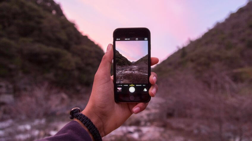 person taking photo with iPhone