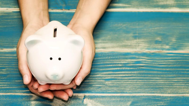 hands holding pig bank on the vintage blue background, a saving money for future investment concept.
