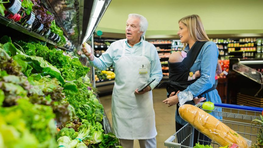 Senior grocery store employee assisting customer in produce section