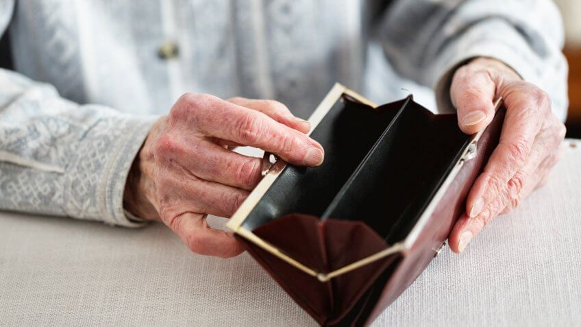 Hands of senior woman, 90 years old, holding empty purse.
