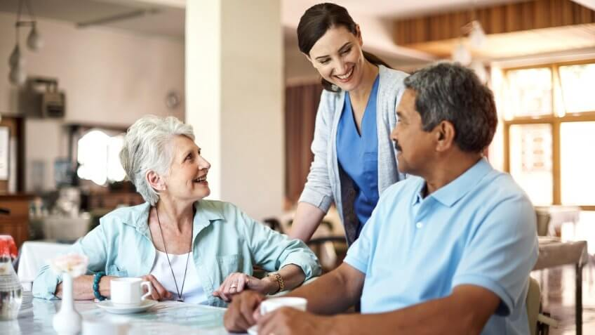 Shot of a young nurse caring for seniors residents in a retirement home.