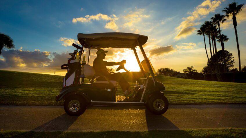 Senior man on golf course driving golf cart at sunrise.