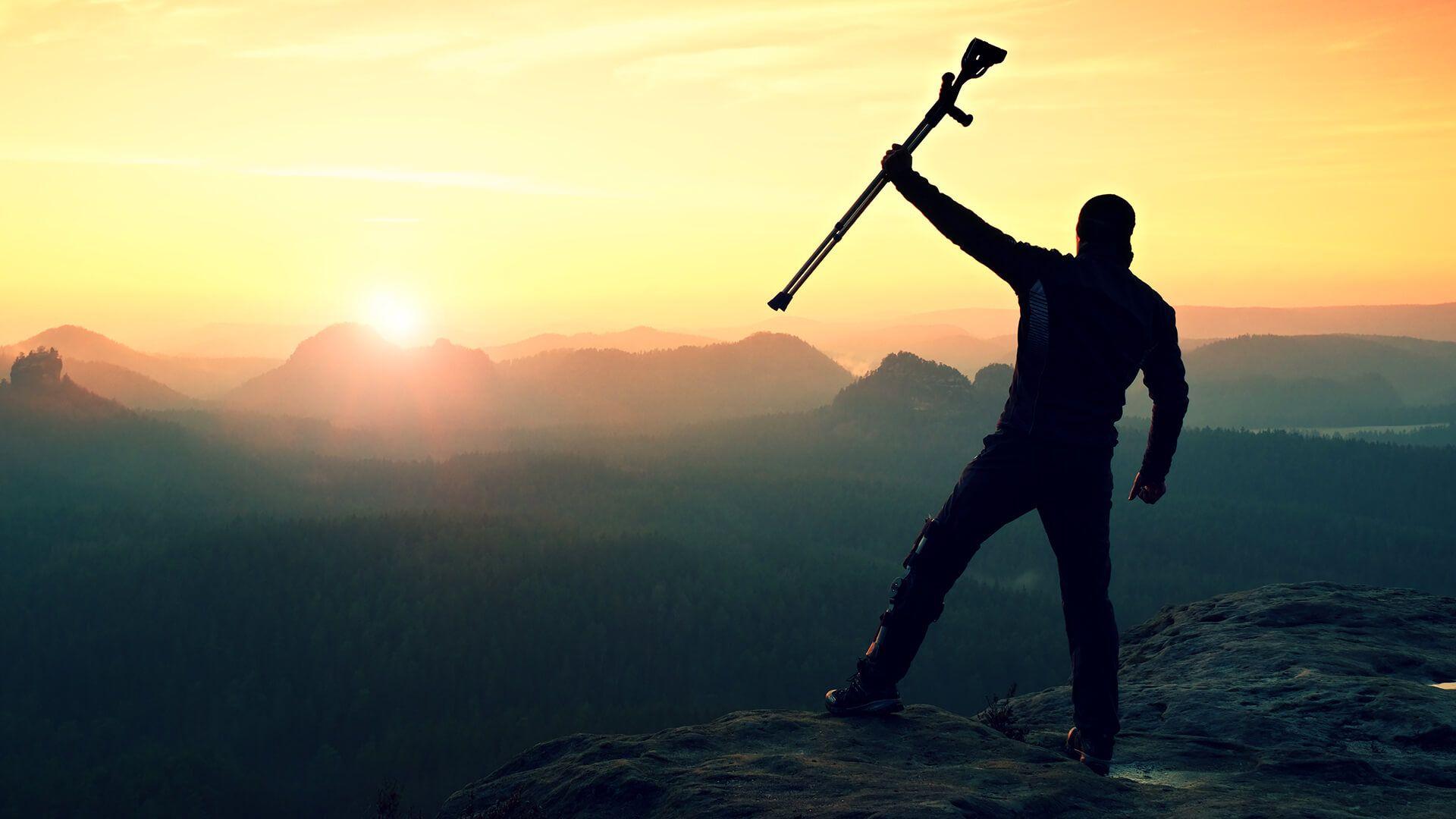 Tourist with forearm crutch above head achieved mountain peak.