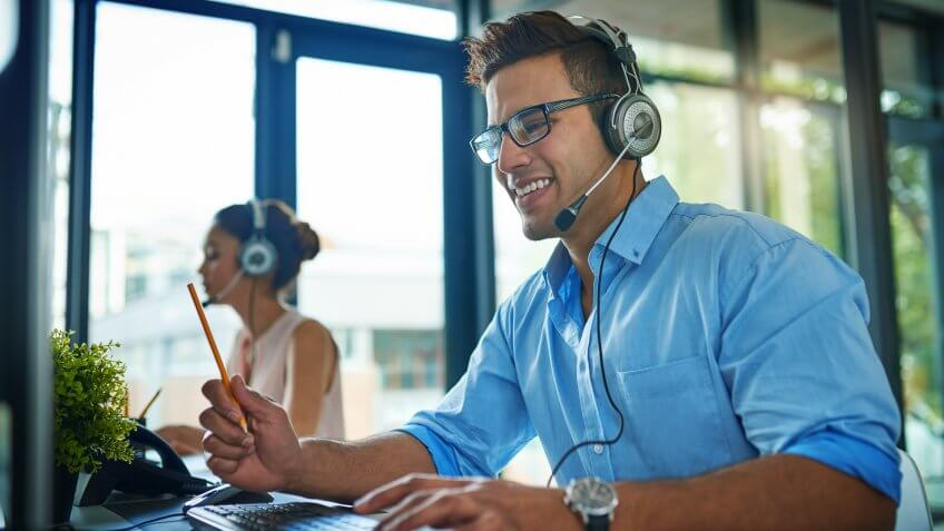 Shot of a young man working in a team of call center agents.
