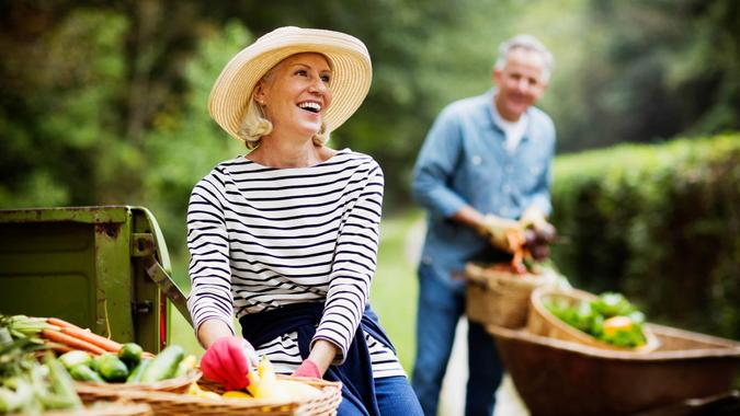 Portrait of mature woman with baskets of harvested vegetables and man working in the background.