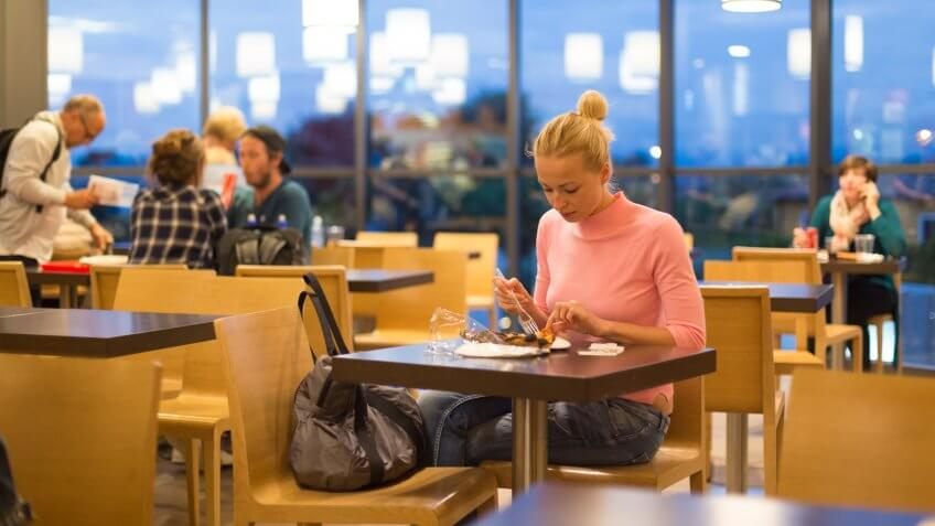 woman eating food in airport cafeteria