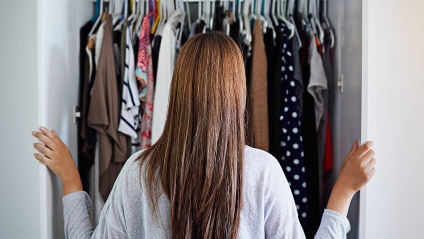 woman looking in unorganized closet