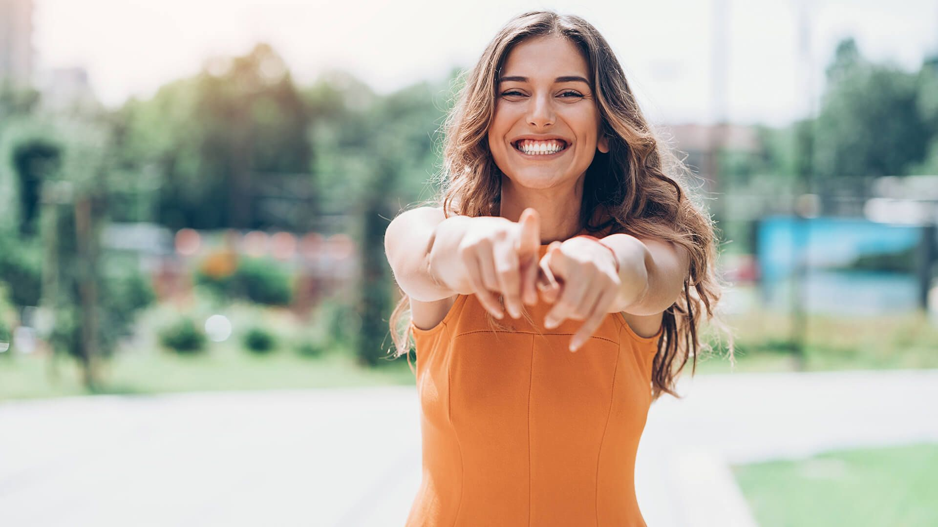 young woman outdoors on a sunny day pointing