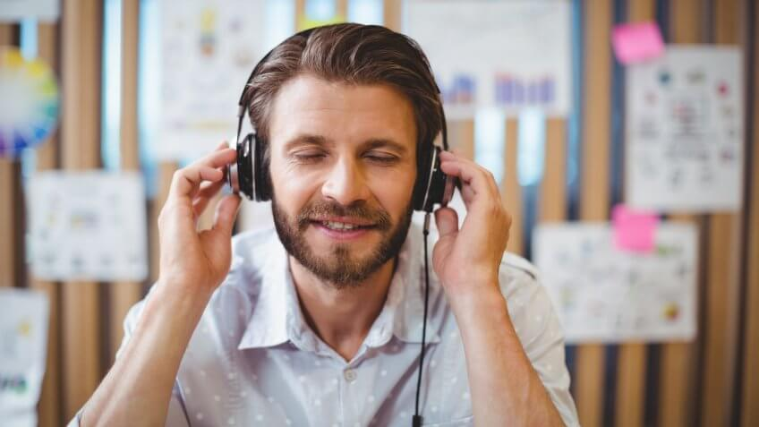 Close-up of male graphic designer listening music on headphone in office.