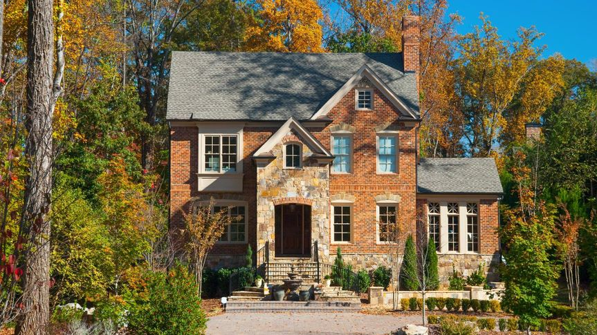 A brick house in the city of Atlanta, GA with a look like it's in the woods / a forest, characteristic of the look of northern Atlanta.