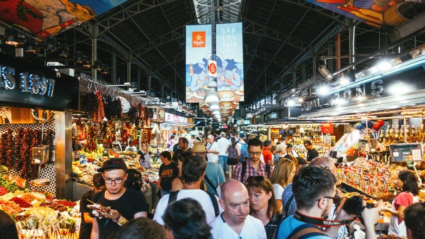 Barcelona, Spain - September 29, 2016: Tourists visiting the Boqueria Market, the most famous market in Barcelona.
