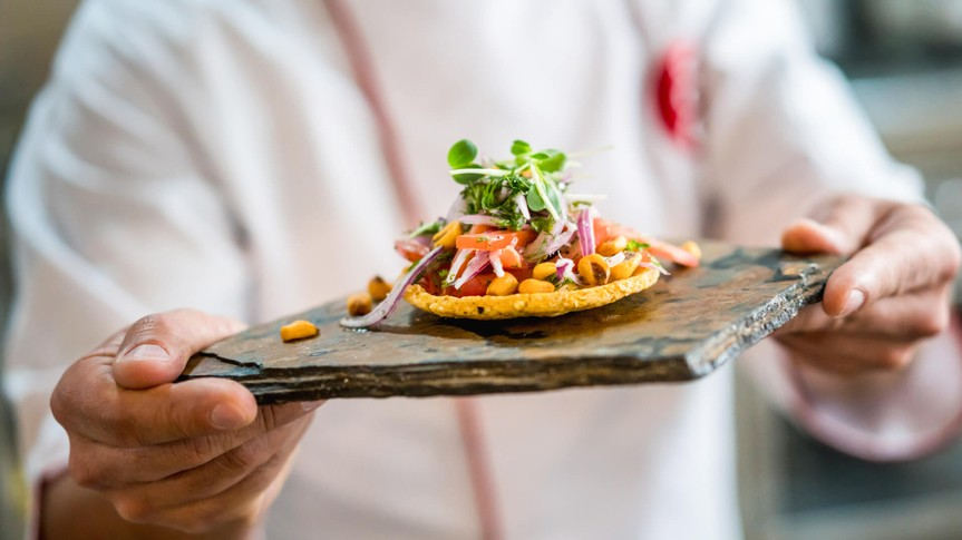 Close-up on a chef serving a small plate at a restaurant -? food and drinks concepts.
