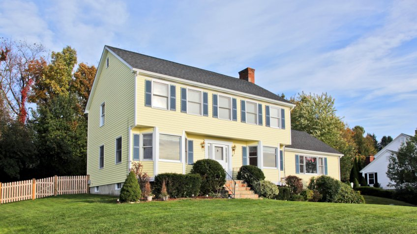 Yellow New England Style colonial house.