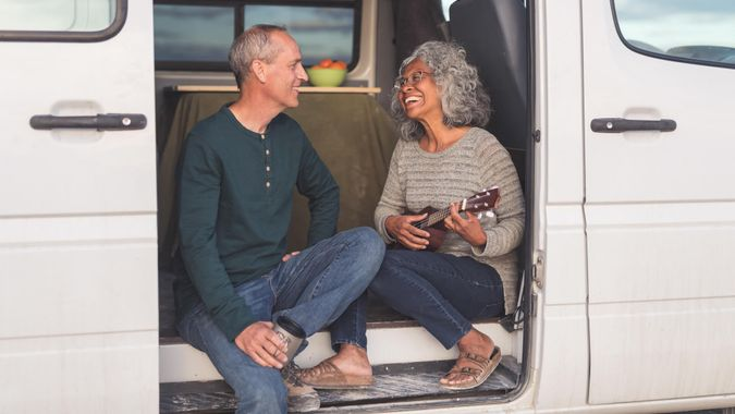 Senior couple sit in the doorway to their camper van while taking a break from driving. The couple is on a road trip in celebration of recently retiring. The ethnic woman strums a ukulele while singing her husband a song. Her husband is affectionately looking at her. He is holding a coffee cup. A portion of the interior of the van is visible. It is cloudy outside. The couple is dressed in casual clothing and the woman is wearing glasses.