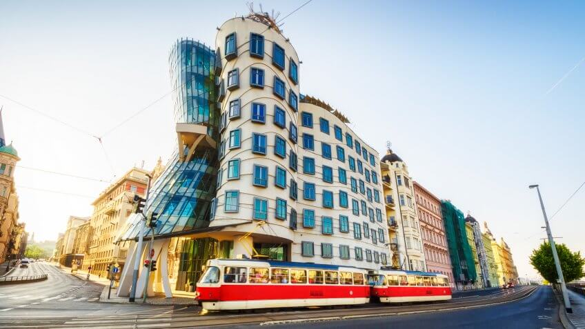 26 may 2018: Red tram passing in front of Dancing House building in Prague.
