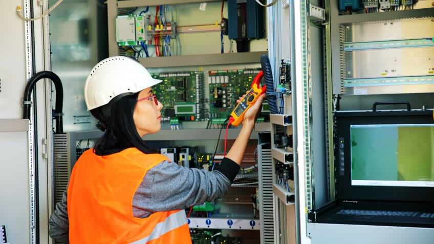 Young female maintenance engineer testing voltage.