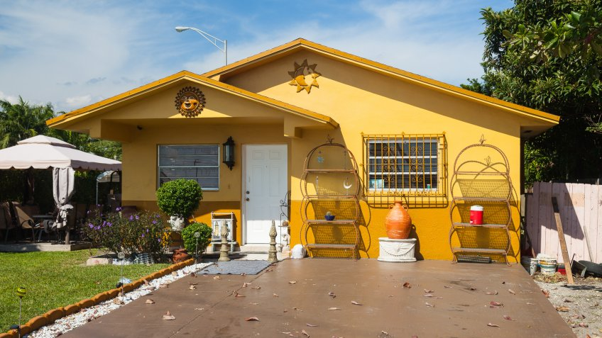 Hialeah, Miami, Florida, USA - November 4, 2012: Yellow House with ornaments in the front and wide driveway.