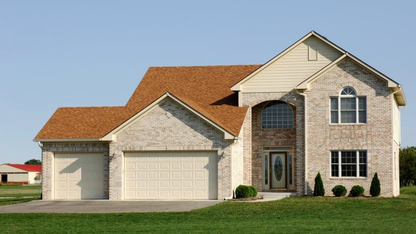 Two story light colored brick home with 3 car garage in suburbia.