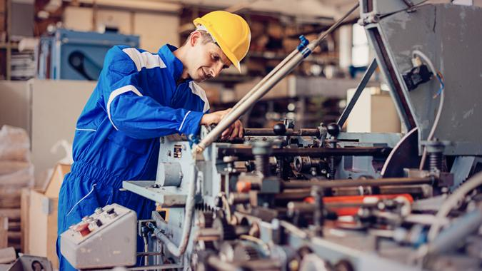 Maintenance engineer or blue collar worker working in production factory, testing and repairing machines, testing roll bars and using grinder or drill.