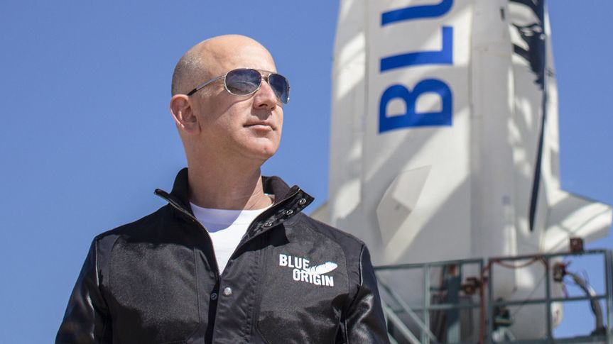 Jeff Bezos stands in front of Blue Origin shuttle