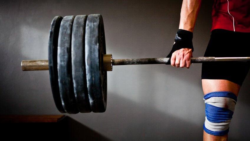 man lifting barbell and disks