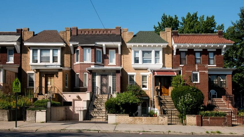 This is a horizontal, color photograph of brick homes in the Astoria neighborhood of Queens, New York.