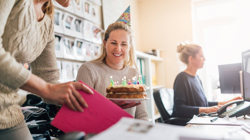 woman sitting at her office desk with a birthday cake handed to her by another female. She is wearing a party hat and smiling.