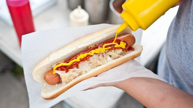 Putting mustard on a hot dog