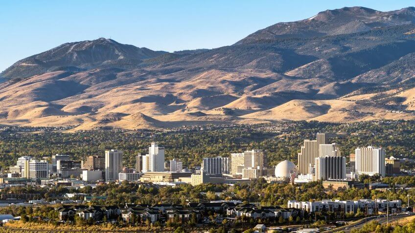 City of Reno Nevada cityscape in early autumn with hotels, casinos, apartments and mountains in the background.