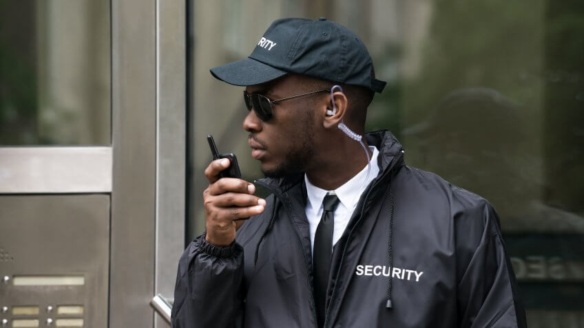 Security guard wearing sunglasses standing in front of entrance speaking into walkie talkie