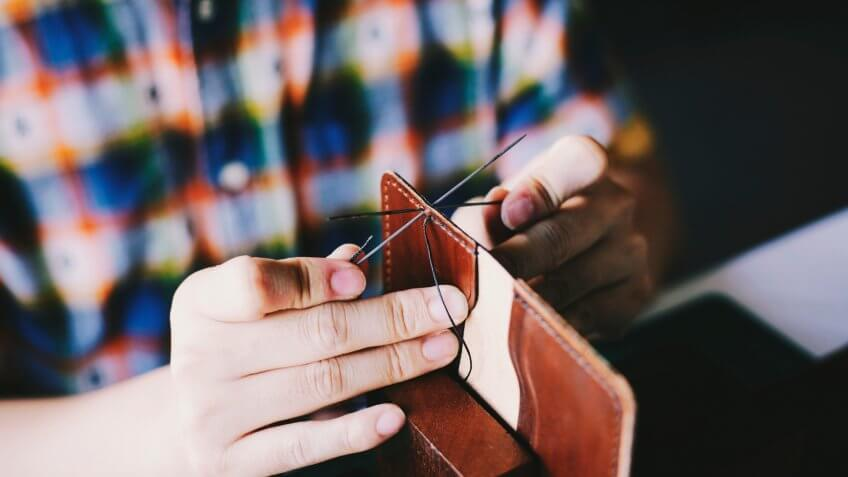 Person sewing together a wallet